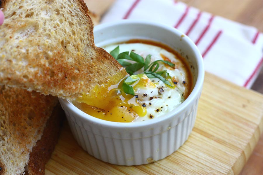 Baked Eggs in Spicy Tomato Sauce with Goat Cheese and Toast